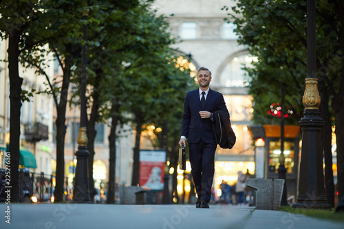 Successful businessman in suit going down central street of modern city