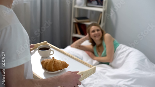 Fotografie, Obraz  Loving husband carrying breakfast in bed, coffee with croissant on tray, romance