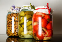 Three Big  Glass Jars With Homemade Canned Tomatoes, Cucumbers, And Dried Apples