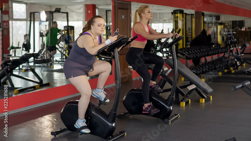 Overweight lady riding sluggishly exercise bike and scrolling smartphone, lazy Canvas Print
