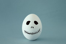 Minimal And Funny Halloween Holiday Concept. White Egg With Scary Cute Face.