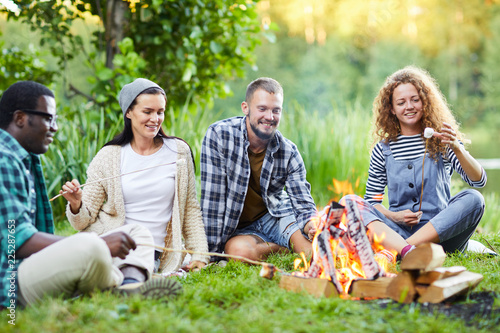 Fotografie, Obraz  Young friendly men and women relaxing by campfire and frying marshmellows in the
