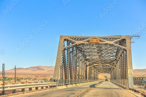 Iron bridge over the railroad in Barstow California on the historic Route 66 with Mojave desert on background Canvas Print