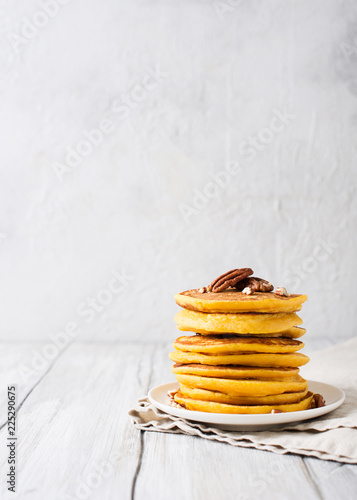 Stack of pancakes with pecan and syrup in nordic style