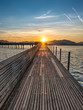 Dramatic sunrise during the Fall Equinox over the historical holzsteg pedestrian bridge crossinhg the Upper Zurich Lake (Obersee), part of the old Way of Saint James, Switzerland