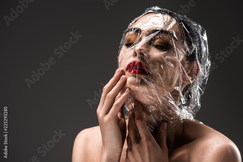 Fotografía  sensual woman with face wrapped in transparent cellophane with drops isolated on