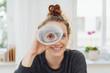 Leinwandbild Motiv junge frau schaut durch ein fernrohr aus papier und lacht