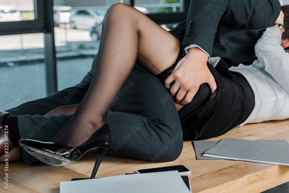 Fototapeta partial view of passionate businessman and businesswoman at workplace in office