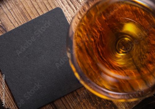Slika na platnu Glass of cognac brandy drink with black coaster on top of wooden barrel