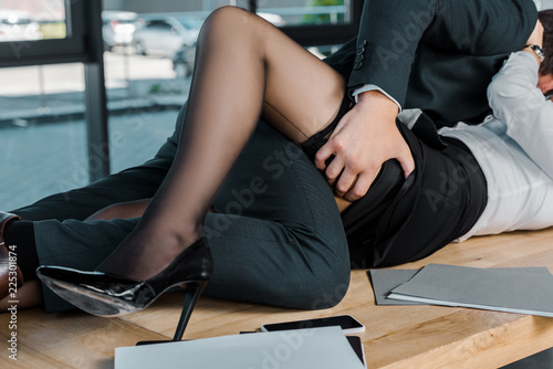 partial view of passionate businessman and businesswoman at workplace in office - fototapety na wymiar