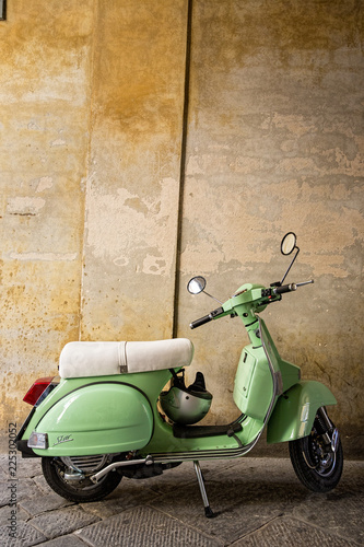 Foto op Plexiglas Toscane Green scooter parked under an archway in a street in Siena, Tuscany