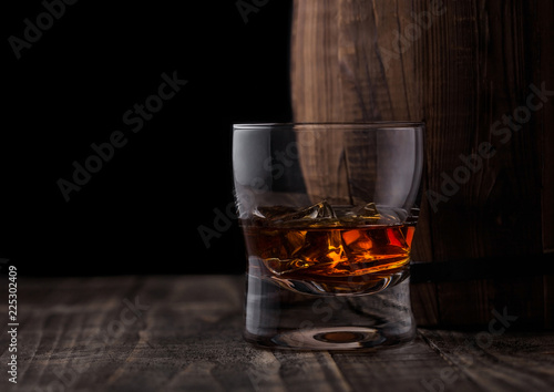 Foto op Plexiglas Bar Glass of whiskey with ice cubes next to wooden barrel. Cognac brandy drink