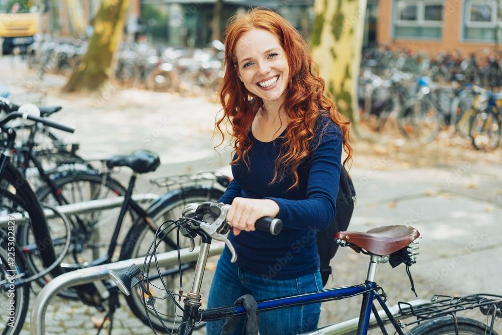 Fototapeta Pretty young redhead student parking her bike