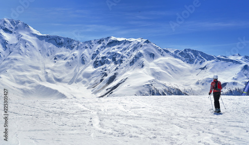 Foto op Canvas Wintersporten skier on a slope in alpine snowy mountain under blue sky