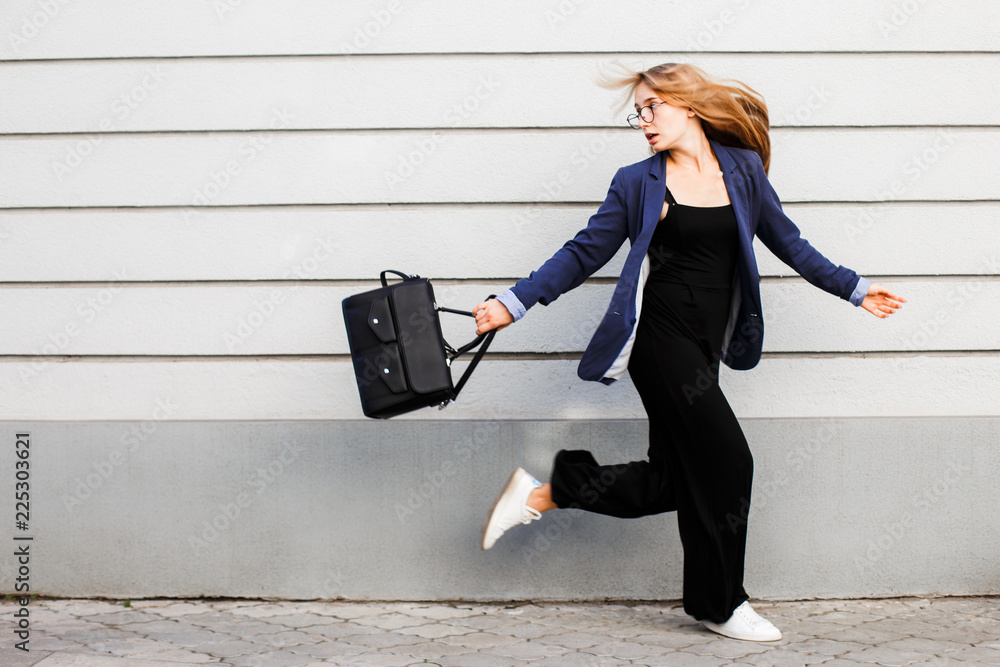 Fototapety, obrazy: Business woman running in a suit with a briefcase along the wall.