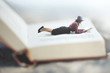 Leinwanddruck Bild - surreal situation of a woman reading her book lying on a giant book