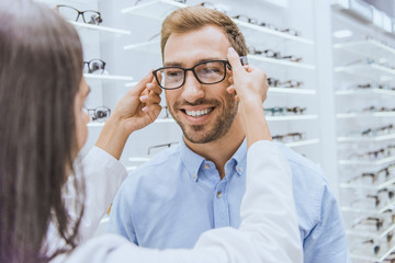 partial view of female optometrist putting on eyeglasses on smiling man in optics