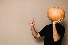 Young Man In Black T-shirt Holding Big Pumpkin In Front Of His Face