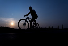 Silhouette Of Boy On The Bike. Young Cyclist Is Jumping On His Bike During Sunset.