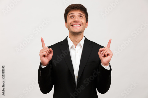 Cheerful young businessman standing isolated over white background wall pointing Poster Mural XXL