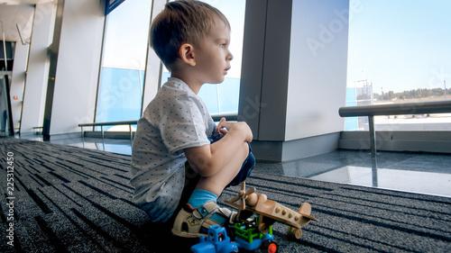 Zdjęcie XXL Portret mały berbeć chłopiec czekanie dla lota obsiadania na podłoga przy lotniskiem