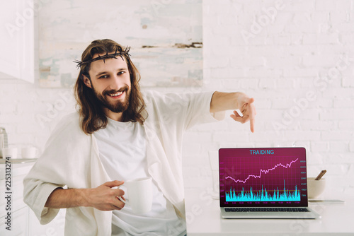 Valokuva smiling Jesus holding cup of coffee and pointing at laptop with trading on scree
