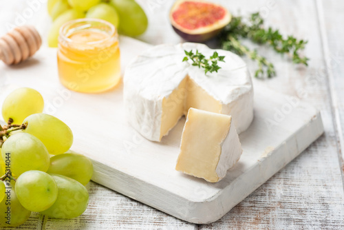 Cheese plate with brie, camembert, honey and fruits, close up view, selective focus. Gourmet appetizer plate