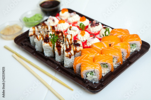 Japanese food rolls in plastic box. Sushi set in a plastic package close up isolated on a white background. Sushi for take away or sushi delivery.