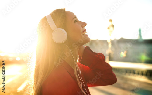 Photo  Beautiful girl listening music with headphones while walking in the street