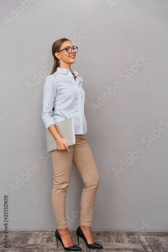 Papiers peints Akt Happy business young woman posing isolated over grey wall background holding laptop computer.