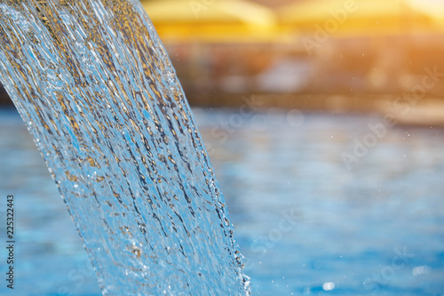 Stream of water in the pool. Blue surface, spray, close-up. Selected focus.
