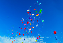 A Lot Of Flying Balloons With Helium In Blue Sky With Clouds