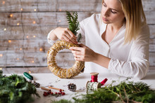 A Young Woman Making A Christmas Wreath.