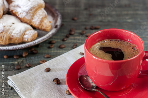Canvas Print Cup of cappuccino coffee and croissant on dark table