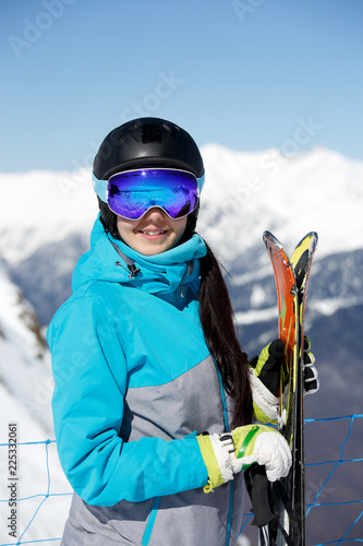 Fotografiet  Image of young smiling female athlete in helmet with skis in hand against blue s