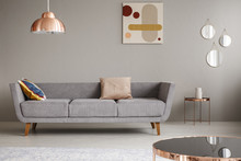 Real Photo Of A Simple Couch With Pillows In A Living Room Decorated With Copper Lamp, Mirror And Painting