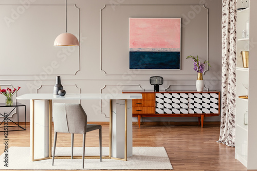 Photo Real photo of a dining room interior with a table, pink painting and vintage cab