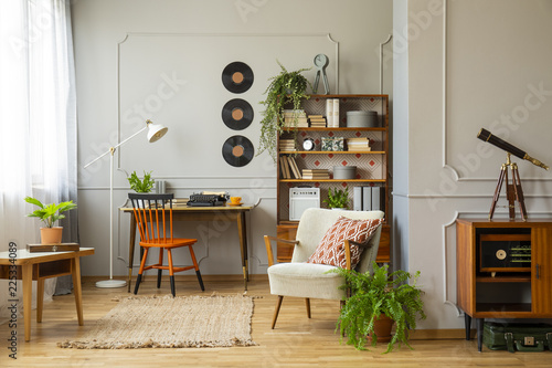 Obraz Rug between armchair and wooden table in retro apartment interior with chair at desk. Real photo - fototapety do salonu