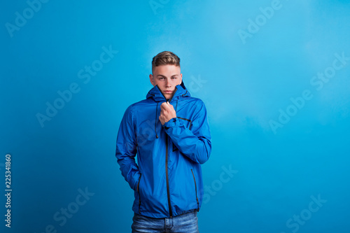 Portrait of a young man with blue anorak in a studio, feeling cold Canvas Print