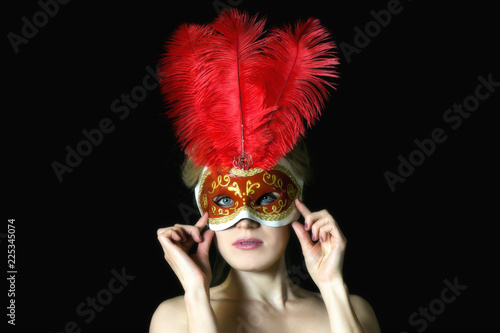 In de dag Carnaval The girl European appearance in the carnival mask. A blond woman in a beautiful mask with feathers on a black background.