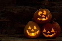 Three Pumpkin Jack-O-Lantern With Happy Faces. Carved Halloween Pumpkins With Burning Candles Inside. Halloween Festive Decorations.