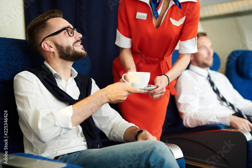 Photo Portrait of handsome businessman smiling while taking coffee served by flight at