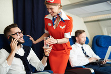Portrait Of Smiling Flight Attendant Serving Glass Sparkling Water To Handsome Businessman Enjoying First Class Trip, Copy Space