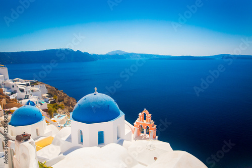 Oia town on Santorini island, Greece. Traditional and famous houses and churches with blue domes over the Caldera, Aegean sea (color toned image)