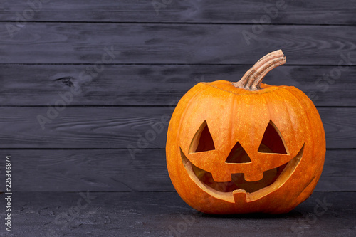 Halloween pumpkin with happy expression. Halloween pumpkin head with smile on black background, copy space. Halloween carving ideas. Halloween greeting card.