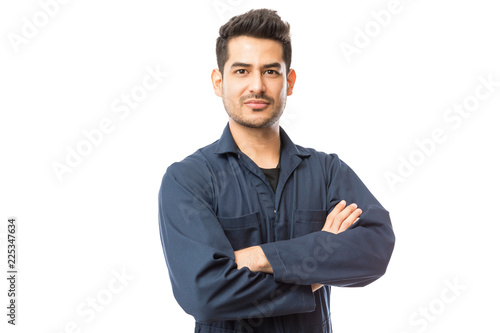 Fotografía  Confident Mechanic Standing Arms Crossed Against White Background