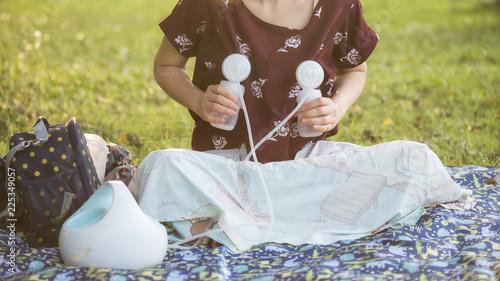 Fotografie, Tablou Mother pump breastmilk in park at sunset