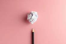 Pencil And A Crumpled Paper Ball On Pink Paper Background. - Business Concept, Symbol Of Key Point And Ideas.