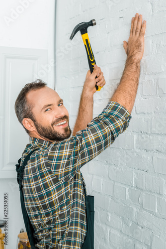 Fotografie, Obraz smiling handsome repairman hammering nail in white wall and looking at camera