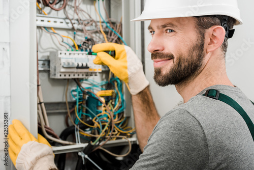 Fotografia  handsome cheerful electrician repairing electrical box and using screwdriver in
